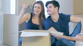 The joy of moving into the house. A loving couple holding box in hands and looking in the box while a young and beautiful couple in love sitting on the couch stock footage