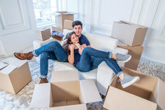 The joy of moving into the house. A loving couple holding box in Stock Image