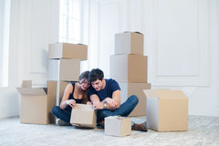 The joy of moving into the house. A loving couple holding box in Stock Photo