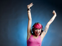 The joy of music. Tattooed girl raising her hands and waving for the joy of music Royalty Free Stock Photo