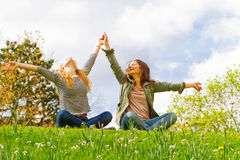 Joy in the park. Young carefree women with raised arms Royalty Free Stock Photo