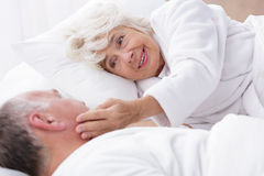 Joy of the possibility of waking up with him for so many years stays unchanged. Elderly couple lying in bed in the morning. Woman is gently touching her husband stock photography
