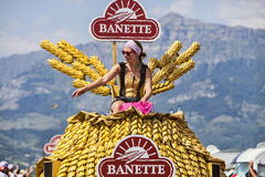 The Joy of Publicity Caravan. Col de Manse, France- July 16, 2013: A young woman throwing out gifts to audience from the fancy Banette's vehicle during the Stock Image