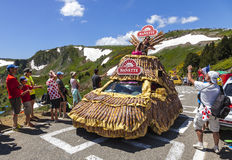 The Joy of Publicity Caravan. Col de Pailheres,France- July 06 2013:A young woman throwing gifts to audience from a fancy Banette's vehicle on the road to Col de Stock Photos