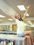 The Joy of Reading. A cute girl with braces in the library celebrating the joy of reading