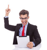 The joy of reading the good news on the tablet. Young business man wearing glasses screaming of joy while reading the good news on the tablet pad Royalty Free Stock Photography