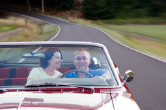 Joy Ride. A wife looks at her husband with love as they drive their vintage red convertible down a country road. Subjects are placed in the lower corner to allow Royalty Free Stock Photo
