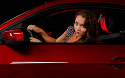 Joy ride. A beautiful young woman caught making a turn in a red sports car at night with the reflection of a red light she could possibly be running in the car Stock Photo