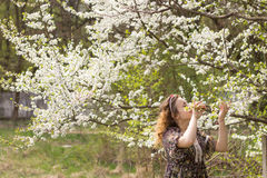 The joy of spring. Happy girl near the blossoming apple tree Stock Photography