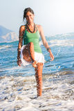 Joy summer. Girl playing on the seashore. Sea and holidays. A smiling young woman is playing with the sea water. She shot the waves splashing. Blue sky stock images