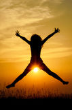 Joy in the sunset. Silhouette of a girl jumping of joy in the warm sunset light with the sun in front of her Royalty Free Stock Images