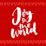 Joy to the world. Christmas greeting card with brush calligraphy. Handwriting on red knitted background Royalty Free Stock Images