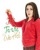 Joy to the World. Close-up of an expressive teen girl in her pajamas holding up a glittery Joy to the World decoration for the viewer to see. On a white stock photography