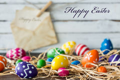 Joy to the world, Easter has come!. Decoration with color easter eggs and raffia, light planks and card in the background royalty free stock photography