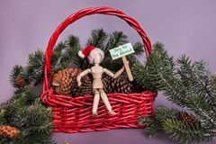 Joy to the world picket sign held by Wooden jointed doll wearing a Santa Claus hat Christmas scene. Red basket pinecones and pine tree limbs royalty free stock photos