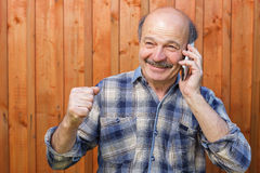 Joy winnings or prize. Elderly man talking on the phone and receives a message about the good news Stock Photo