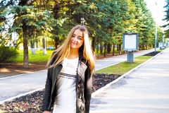 Joy. A young pretty girl with light brown hair depicts different emotions. The girl is dressed in a black leather jacket and a white dress under her. She does royalty free stock image