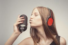 Joyable attractive fashion pretty girl listening music with headphones, and kiss speaker, wearing red gloves, take pleasure with stock photos