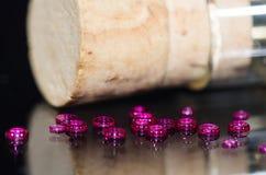 Joyas del agujero recolectadas al lado de un frasco tapado con corcho foto de archivo libre de regalías