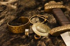 Joyas y espada escandinavas en una piel Imagen de archivo