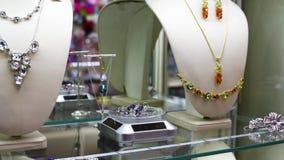 Joyería con las piedras y los diamantes artificiales en las gemas del estante en joyería almacen de video
