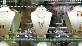 Joyería con las piedras y los diamantes artificiales en las gemas del estante en joyería metrajes