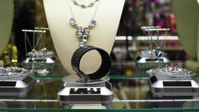 Joyería con las piedras y los diamantes artificiales en las gemas del estante en joyería almacen de metraje de vídeo
