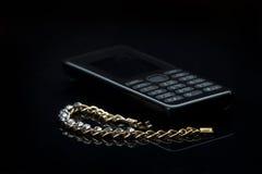 Joyería con un teléfono celular en fondo de la oscuridad de la pendiente Imagen de archivo