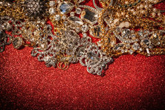Joyería de oro y de plata en fondo brillante rojo del brillo foto de archivo