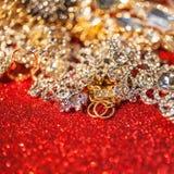 Joyería de oro y de plata en fondo brillante rojo del brillo Imágenes de archivo libres de regalías