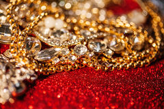 Joyería de oro y de plata en fondo brillante rojo del brillo Fotos de archivo