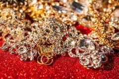 Joyería de oro y de plata en fondo brillante rojo del brillo Foto de archivo libre de regalías
