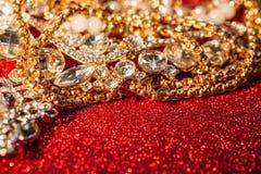 Joyería de oro y de plata en fondo brillante rojo del brillo Imagen de archivo libre de regalías