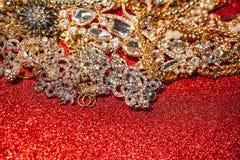 Joyería de oro y de plata en fondo brillante rojo del brillo Imagen de archivo