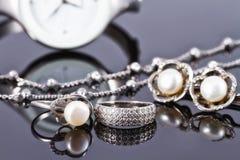 Joyería de plata con las perlas y los relojes de las mujeres elegantes Foto de archivo
