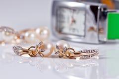 Joyería del oro con las perlas y los relojes de las mujeres elegantes Imagenes de archivo