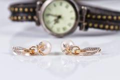 Joyería del oro con las perlas y los relojes de las mujeres elegantes Imagen de archivo libre de regalías