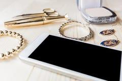 Joyería, maquillaje y teléfono del oro Foto de archivo