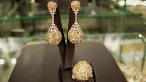Joyería, sistema de la joyería, pendientes y un anillo del oro cubierto con las joyas, regalo elegante costoso, brillante vendido metrajes