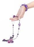 Joyería y pulsera púrpuras con la mano humana Fotografía de archivo