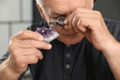 Joyero de sexo masculino que evalúa la piedra preciosa semi preciosa en taller imagenes de archivo