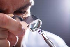 Joyero Looking At Diamond Through Magnifying Loupe imagenes de archivo