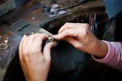 Joyero que trabaja con el anillo de oro del fichero de la aguja en taller de la joyería fotos de archivo