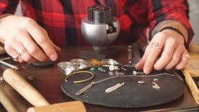 Joyero que trabaja con la cadena en taller hombre talentoso que repara el collar para el cliente almacen de metraje de vídeo
