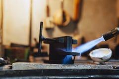 Joyero que usa tacto para calentar las herramientas de la soldadura Foto de archivo