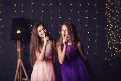 Joyeuse amie Deux filles dans le rose et robes pourpres montrent chut, dans le studio sur le fond foncé Copiez l'espace Images stock