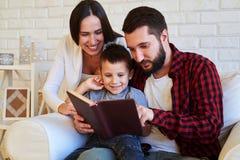 Joyeuse famille regardant le livre Photos stock