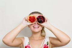 Joyeuse femme blonde ayant l'amusement avec des petits gâteaux dans les mains et le coverin Photo stock