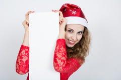 Joyeuse fille dans la robe rouge dans le chapeau de Noël tenant des bannières Photos libres de droits