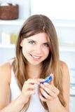 Joyeuse jeune femme utilisant la crème pour ses languettes image stock
